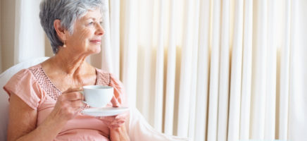 Senior lady with coffee cup looking to her side at copyspace