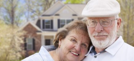 20725850 - attractive happy senior couple in front yard of house.